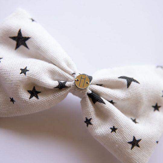 Prendedor con lazo en color beige con estrellas negras